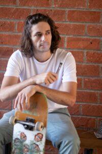 Mann mit Skateboard und E-Zigarette